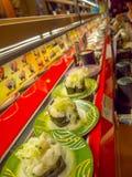 TOKYO, JAPAN -28 JUN 2017: Sluit omhoog van geassorteerd japanesse voedsel over een lijst, binnen van een sushi van de kaitenzush Royalty-vrije Stock Afbeeldingen
