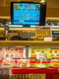 TOKYO, JAPAN -28 JUN 2017: Sluit omhoog van geassorteerd japanesse voedsel over een lijst, met het scherm met het menu, binnen va Stock Foto