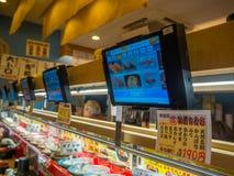 TOKYO, JAPAN -28 JUN 2017: Sluit omhoog van geassorteerd japanesse voedsel over een lijst, met het scherm met het menu, binnen va Stock Afbeeldingen