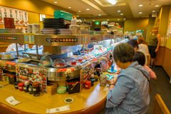 TOKYO, JAPAN -28 JUN 2017: Unidentified people eating an assorted japanesse food over a table, inside of a kaitenzushi. Conveyor belt sushi restaurant royalty free stock image