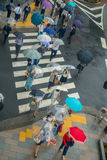 TOKYO, JAPAN JUNE 28 - 2017: Aerial view of unidentified people under umbrellas on zebra crossing street in Jimbocho Royalty Free Stock Photo