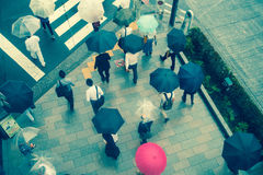 TOKYO, JAPAN JUNE 28 - 2017: Aerial view of unidentified people under umbrellas on zebra crossing street in Jimbocho Stock Photo