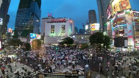 Tokyo, Japan - June 20, 2018 : Time lapse video of people with umbrellas cross the famous diagonal intersection in Shibuya, Tokyo
