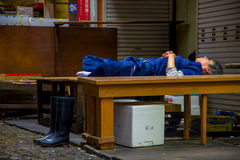 TOKYO, JAPAN JUNE 28 - 2017: Unidentified man wearing a blue clothes and taking a nap over wooden table inside of a Fish Royalty Free Stock Image