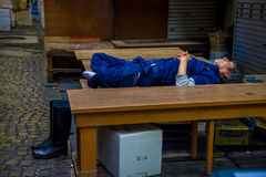 TOKYO, JAPAN JUNE 28 - 2017: Unidentified man wearing a blue clothes and taking a nap over wooden table inside of a Fish Stock Photography
