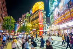 TOKYO, JAPAN JUNE 28 - 2017: Unidentified people crossing the street in Kabukicho red lights district, surrounding of. Big buildings and advertisements in the Royalty Free Stock Photos