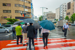 TOKYO, JAPAN JUNE 28 - 2017: Unidentified people under umbrellas on zebra crossing street in Jimbocho district located Stock Images
