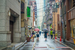 TOKYO, JAPAN JUNE 28 - 2017: Unidentified people under umbrellas on zebra crossing street in Jimbocho district located Royalty Free Stock Photography