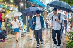 TOKYO, JAPAN JUNE 28 - 2017: Unidentified people walking under the rain in the sidewalk with umbrellas in Jimbocho Stock Images