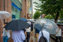 TOKYO, JAPAN JUNE 28 - 2017: Unidentified people walking under the rain in the sidewalk with umbrellas in Jimbocho Royalty Free Stock Images
