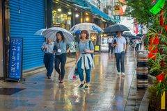 TOKYO, JAPAN JUNE 28 - 2017: Unidentified people walking under the rain in the sidewalk with umbrellas in Jimbocho Stock Photo