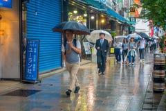 TOKYO, JAPAN JUNE 28 - 2017: Unidentified people walking under the rain in the sidewalk with umbrellas in Jimbocho Stock Image