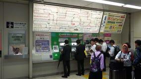 Tokyo Japan - Juni 20, 2018: Köpande drevbiljetter för folk på varuautomater för JRShibuya station arkivfilmer
