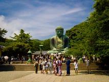 TOKYO, JAPAN JUNI 28 - 2017: Menigte van mensen die en beelden stellen nemen bij monumentaal bronsstandbeeld van Grote Boedha Stock Afbeeldingen