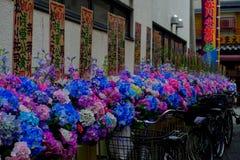 TOKYO, JAPAN JUNI 28 - 2017: Mooie kleurrijke plastic bloemen, op een rij in in openlucht dichtbij van de Boeddhistische Tempel Stock Afbeelding