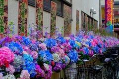 TOKYO, JAPAN JUNI 28 - 2017: Mooie kleurrijke plastic bloemen, op een rij in in openlucht dichtbij van de Boeddhistische Tempel Royalty-vrije Stock Fotografie