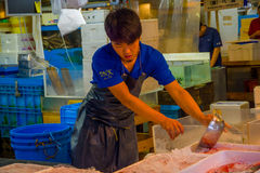 TOKYO, JAPAN AM 28. JUNI - 2017: Nicht identifizierter Mann, der blaue Kleidung und delantal, Manipulierungseis mit einem metalli Lizenzfreie Stockfotografie