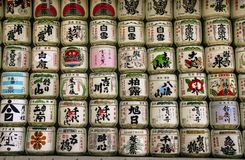 TOKYO, JAPAN - MARCH 25, 2019: Collection of Japanese sake barrels stacked is at the japanese shrine Meiji Jingu.  royalty free stock images