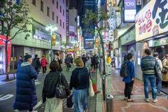 People walking along a side street around Shinjuku station at night stock photography