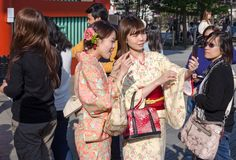 Japanese girls  in traditional dress with mobile phone, do selfie. TOKYO, JAPAN - MARTH 25, 2014: Japanese girl and boy  in traditional dress near the Sensoji stock photography