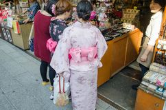 Japanese girls in traditional dress buy souvenirs at Nakamise, shopping street, Tokyo. Japan. TOKYO, JAPAN - MARTH 25, 2014: Japanese girls in traditional dress stock photography