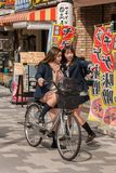 Two Japanese schoolgirls and  bicycle  in Akihabara district, Tokyo, Japan. TOKYO, JAPAN - MARTH 16, 2012: Two Japanese schoolgirls and  bicycle  in Akihabara stock images