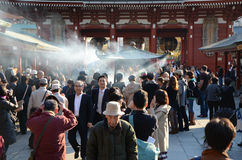 TOKYO, JAPAN - NOV 21: Buddhists gather around a fire to light incense and pray at Sensoji Temple Royalty Free Stock Photo