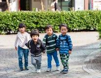 TOKYO, JAPAN - NOVEMBER 7, 2017: Four children in a city park. Copy space for text. TOKYO, JAPAN - NOVEMBER 7, 2017: Four children in a city park. Copy space royalty free stock photos