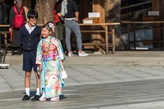 TOKYO, JAPAN - NOVEMBER 7, 2017: A girl and a boy are photographed on the territory of the temple. Copy space for text. TOKYO, JAPAN - NOVEMBER 7, 2017: A girl royalty free stock images
