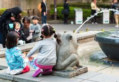 TOKYO, JAPAN - NOVEMBER 7, 2017: The girls are sitting near the fountain. TOKYO, JAPAN - NOVEMBER 7, 2017: The girls are sitting near the fountain stock photos