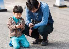 TOKYO, JAPAN - NOVEMBER 7, 2017: A man and a boy are sitting on. The floor in a city street. Copy space for text stock photography