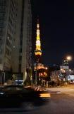 Tokyo, Japan - November 28, 2013: Mening van bezige straat bij nacht met de toren van Tokyo Stock Foto's