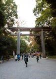 TOKYO, JAPAN - NOVEMBER 23, 2013: Toeristenbezoek de Torii-Poort die zich bij de ingang aan Meiji Jingu Shrine bevinden Royalty-vrije Stock Afbeeldingen