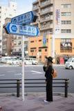 TOKYO, JAPAN - 13. November 2017: Touristenmädchenblick auf Straßenschild zum buddhistischen Tempel Sensoji, Japan Der Sensoji-Te Lizenzfreie Stockfotos