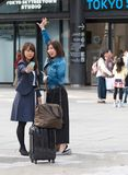 TOKYO, JAPAN - NOVEMBER 7, 2017: Two girls with suitcases take pictures of themselves. Vertical. Copy space for text. royalty free stock photo