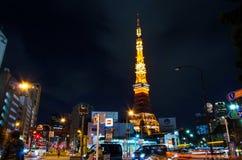 Tokyo Japan - November 28, 2013: Upptagen gata på natten med det Tokyo tornet Fotografering för Bildbyråer