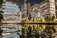 TOKYO, JAPAN - OCTOBER 6, 2015: Business Buildings and reflection on water. Night photo with long exposure in Tokyo, Japan. Business Buildings and reflection on Royalty Free Stock Photos
