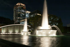 TOKYO, JAPAN - OCTOBER 6, 2015: Fountain ant night witl lights and business office building in background. Fountain ant night witl lights and business office Royalty Free Stock Photo