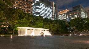 TOKYO, JAPAN - OCTOBER 6, 2015: Fountain at night with business buildings in background. Long exposure photo. Fountain at night with business buildings in Royalty Free Stock Photography