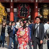 TOKYO, JAPAN - OCTOBER 31, 2017: Girl in a red kimono near the temple Senso-ji. TOKYO, JAPAN - OCTOBER 31, 2017: Girl in a red kimono near the temple Senso-ji Stock Photo
