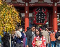TOKYO, JAPAN - OCTOBER 31, 2017: Girl in a red kimono near the temple Senso-ji. TOKYO, JAPAN - OCTOBER 31, 2017: Girl in a red kimono near the temple Senso-ji Royalty Free Stock Photo