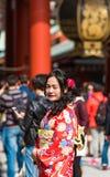 TOKYO, JAPAN - OCTOBER 31, 2017: Girl in a red kimono near the temple Senso-ji. Vertical. TOKYO, JAPAN - OCTOBER 31, 2017: Girl in a red kimono near the temple Stock Photos