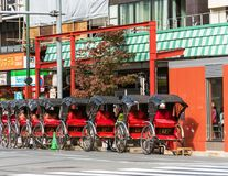TOKYO, JAPAN - OCTOBER 31, 2017: Parked rickshaws in a row on a city street. Copy space for text. stock photos