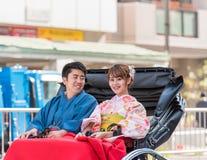 TOKYO JAPAN - OKTOBER 31, 2017: Koppla ihop i en rickshaw på en stadsgata Kopiera utrymme för text Royaltyfri Bild