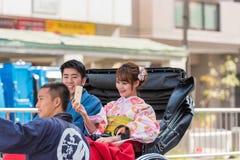TOKYO JAPAN - OKTOBER 31, 2017: Koppla ihop i en rickshaw på en stadsgata Kopiera utrymme för text Arkivfoton