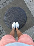 Top view of female legs standing on a manhole in Nagano, Japan stock image