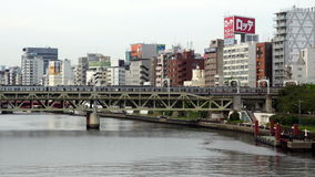 Tokyo Japan. Time Lapse of Passenger Train Passing Tokyo Skyline Daytime - Tokyo Japan stock video