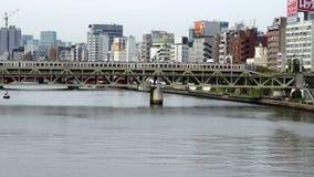 Tokyo Japan. Time Lapse of Passenger Train Passing Tokyo Skyline Daytime - Tokyo Japan stock footage