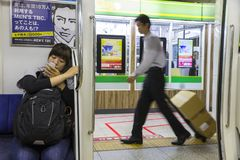 Tokyo Subway scene. Tokyo, Japan. Typical scene at the Tokyo Subway, with a sit young girl looking at her mobile phone, an advertisement, and a delivery man in royalty free stock images