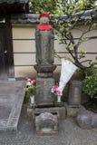 Tokyo, Japon - statue religieuse en pierre paisible de Jizo avec le chapeau rouge Image libre de droits